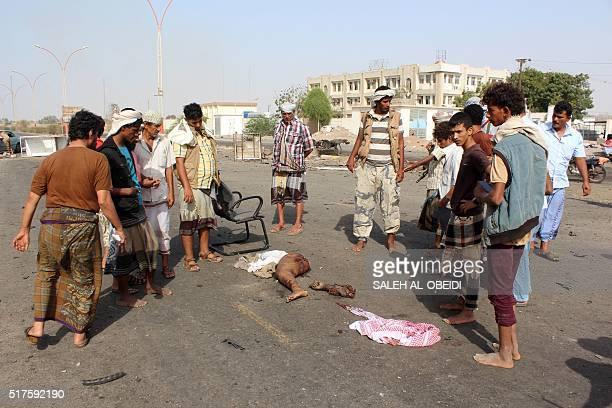 Graphic content / Yemenis take pictures gather around body parts on March 26 2016 at the site of a suicide bomb attack that struck the day before...