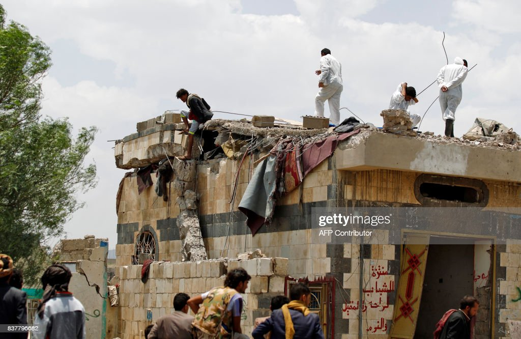 Graphic content / Yemenis watch on as a man tries to approach the body of a man stuck under the collapsed roof of a building hit in an air raid in the Arhab area, around 20 kilometres (13 miles) north of Sanaa, on August 23, 2017, where a Saudi-lead coalition has been bombing Iran-backed Huthi rebels. The Huthis, who control Sanaa along with forces loyal to former president Ali Abdullah Saleh, blamed the pro-government Arab military coalition for the attack on Arhab district. /