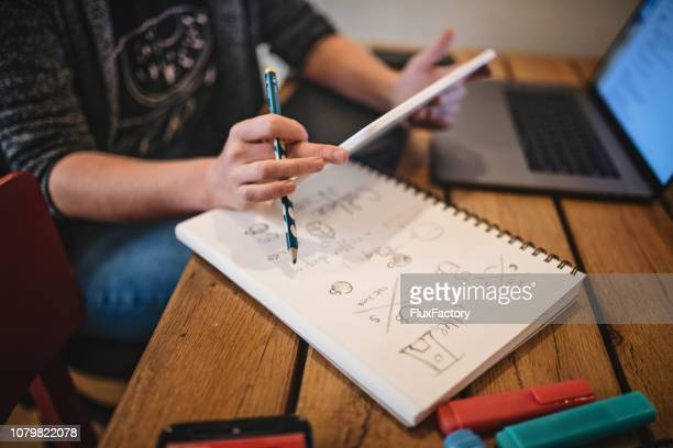 graphic design student studying logo making at home - logo design stock photos and pictures