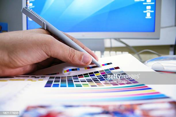 Graphic designer checks the colors on the printed page