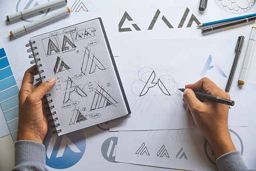 Graphic designer development process drawing sketch design creative Ideas draft Logo product trademark label brand artwork. Graphic designer studio Concept. 1149597075
