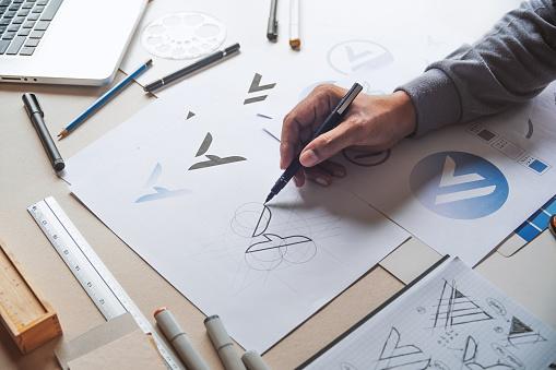 Graphic designer development process drawing sketch design creative Ideas draft Logo product trademark label brand artwork. Graphic designer studio Concept. 1153633370