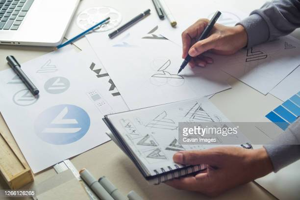 graphic designer drawing sketch design creative ideas draft logo - logo stock pictures, royalty-free photos & images
