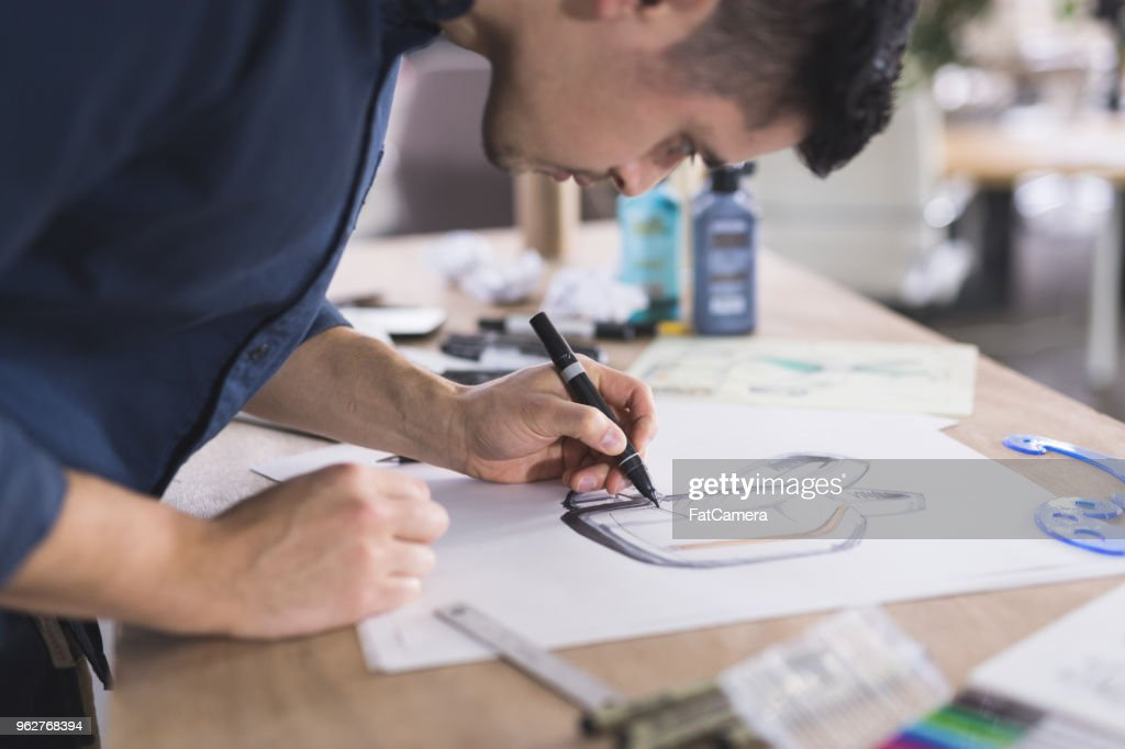 A graphic designer sketches out prototypes for an idea onto paper. He is left-handed and using a pen. There are various pens, papers, and art supplies setting on the desk. The shot is focused on the sketch and includes his hand and his head in profile as he leans over to concentrate.