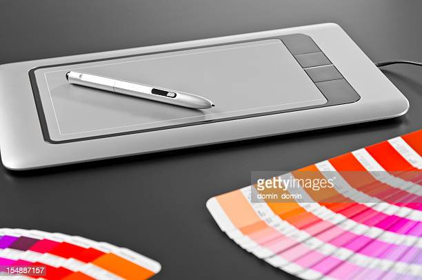 Graphic designer's tools: digital tablet, pen, swatches, dark gray background