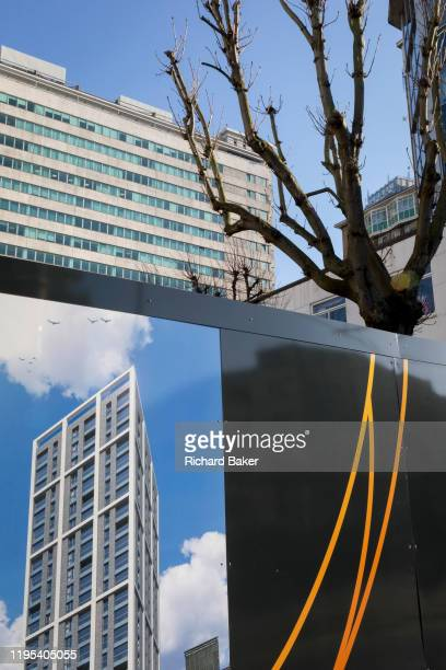 A graphic showing a future apartment highrise to be built by housing trust 'Notting Hill Genesis' is seen on the construction site hoarding beneath...