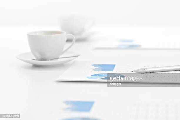 Graphs on paper with cups during a business meeting