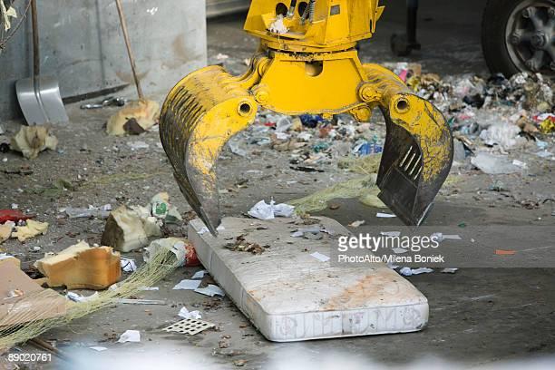 Grapple picking up mattress in garbage dump