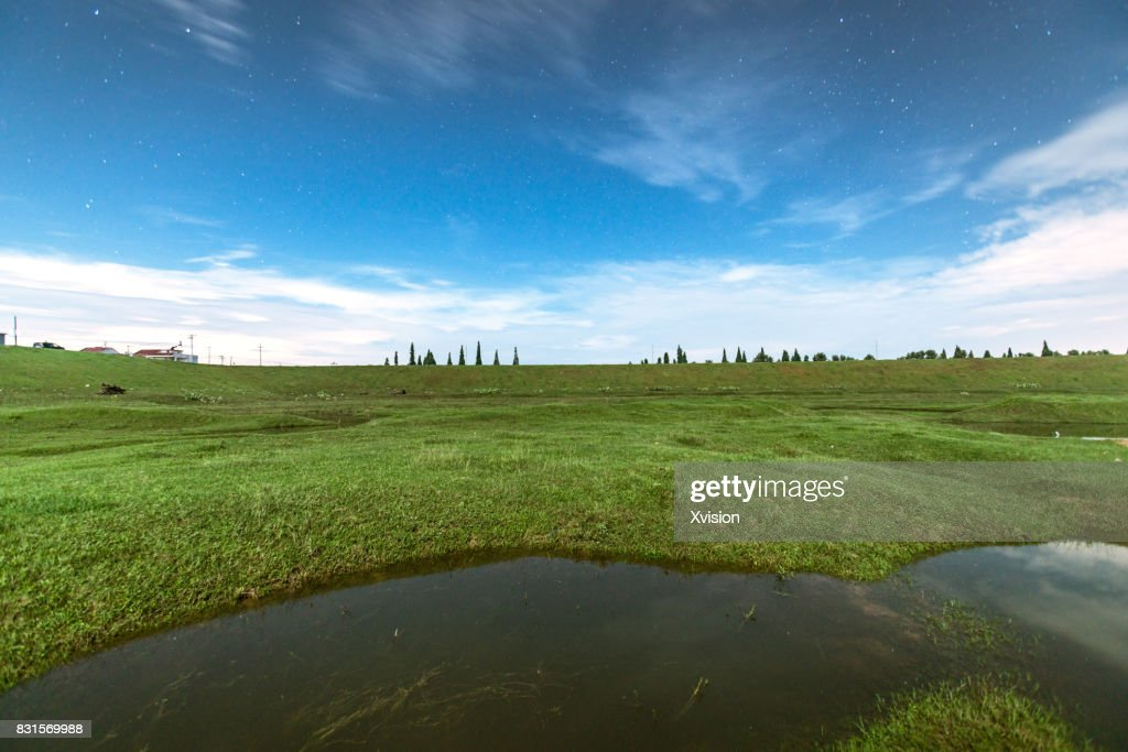 grass field at night. Grass Field With Water Pond Inside It At Night Moon Light : Stock Photo