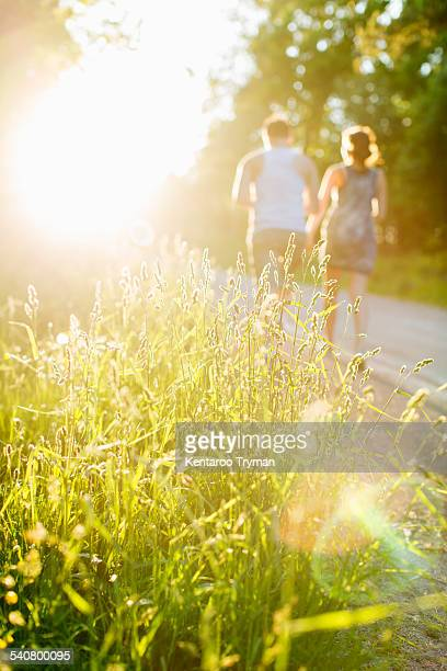 Grass growing in field with couple walking on dirt road in background
