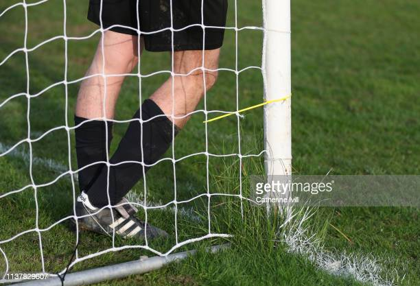Grass grows around the goalpost as the goalkeeper stands in the goal during the Cherry Red Records Combined Counties Football League Division One...