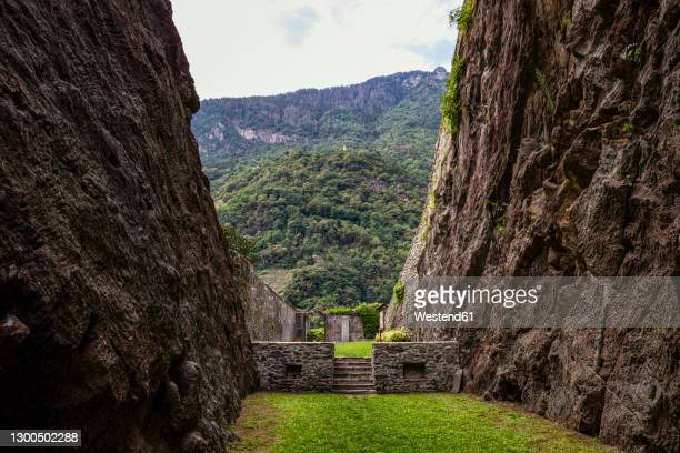 grass lane amidst soapstone cliffs at quarry in parco archeologico botanico del paradiso, valchiavenna, chiavenna, province of sondrio, lombardy, italy - soapstone stock pictures, royalty-free photos & images