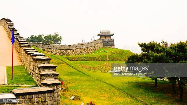 Grass On Lawn And Hwaseong Fortress Against Clear Sky