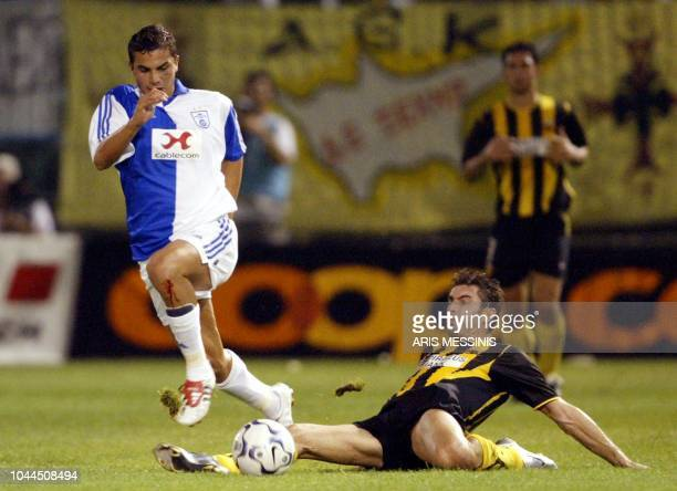 Grasshopper's Magro is tackled by AEK's Thodoris Zagorakis during a second leg qualification game for the Champions League in Athens 27 August 2003...