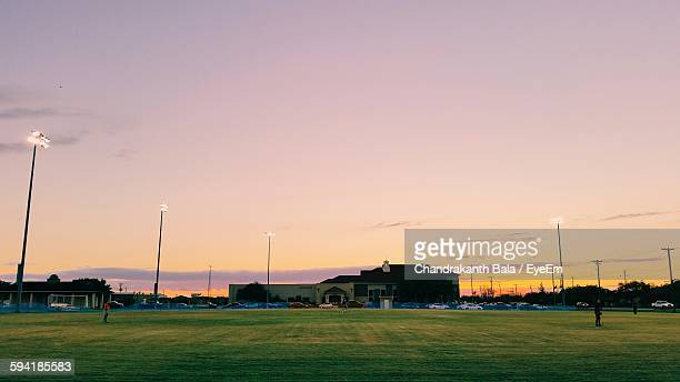 Grassy Ground And Buildings Against Sky During Sunset