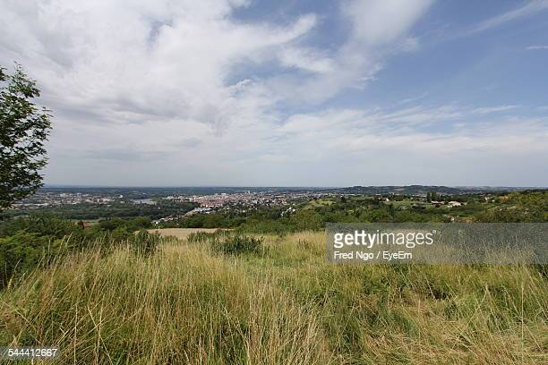 grassy landscape against cloudy sky - vichy stock photos and pictures