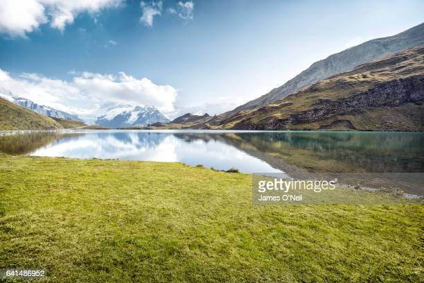 grassy patch next to lake with mountain reflections - berg stock-fotos und bilder