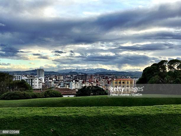 Grassy Rolling Hills Towards The City Against Cloudy Sky