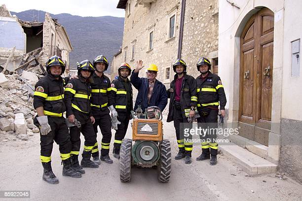 Grateful resident poses with the firemen who retrieved his rotavator from the rubble of his earthquake-damaged home on April 13, 2009 in L'Aquila,...