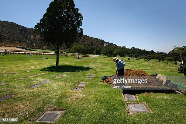 A grave digger prepares for a funeral of an unidentified person at Forest Lawn MemorialParks and Mortuaries Mortuary on July 1 2009 in Los Angeles...