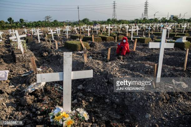Grave digger rests as he buries a coffin of a Covid-19 coronavirus victim at a cemetery in Surabaya on August 9, 2021.