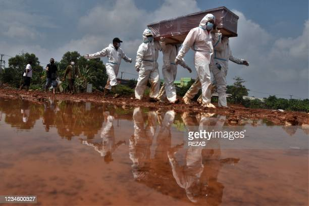 Grave diggers carry the coffin of a victim who died from Covid-19 coronavirus for burial at a cemetery in Bekasi on August 10, 2021.
