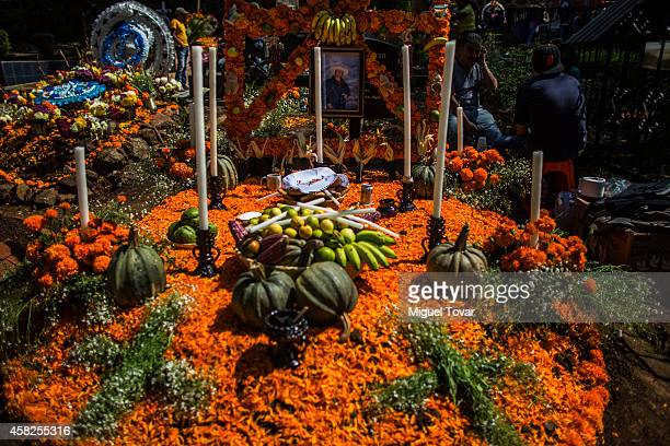 A grave is decorated with cempasuchil flowers and meals in a cemetery at the outskirt of Patzcuaro which people remember those relatives and friends...