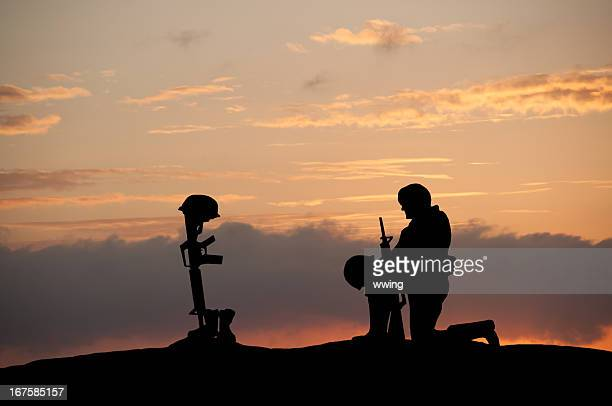 grave of fallen soldier - soldier praying stock photos and pictures