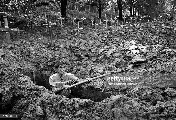 Gravedigger at work in Sarajevo's Lion Cemetery where, prior to the war, lovers met and people walked their dogs. In 1992 an average of 12 citizens a...