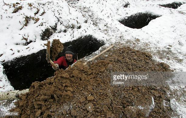 Grave-digger carries out his grim duties for the funerals of some of the 107 miners killed in a methane explosion, March 22, 2007 in the Siberian...
