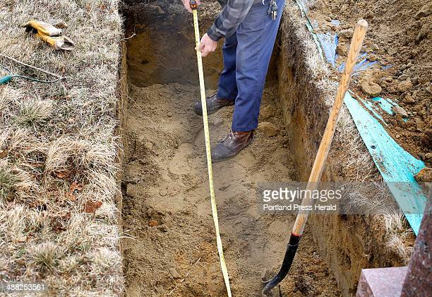 Gravedigger Everard Hall meaures the length of a grave in a cemetery in Cherryfield on April 25, 2014. Hall figures he has dug about 2500 graves.