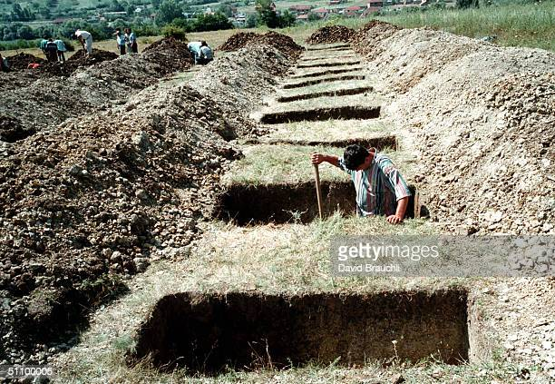 A GraveDigger Shovels Dirt Out Of A Grave While Digging One Of 64 Graves In Kosovo's MidAfternoon Heat Sunday July 4 1999 In Bela Crkva Some 50 Kms...