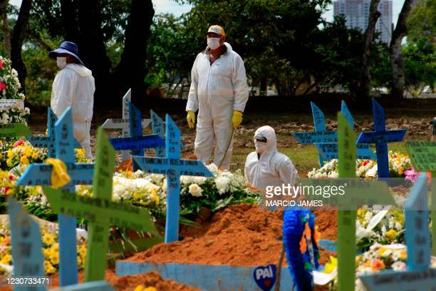 Gravediggers are seen during a funeral of a COVID-19 victim at the Nossa Senhora Aparecida cemetery in Manaus, Amazonas state, Brazil, on January 22...