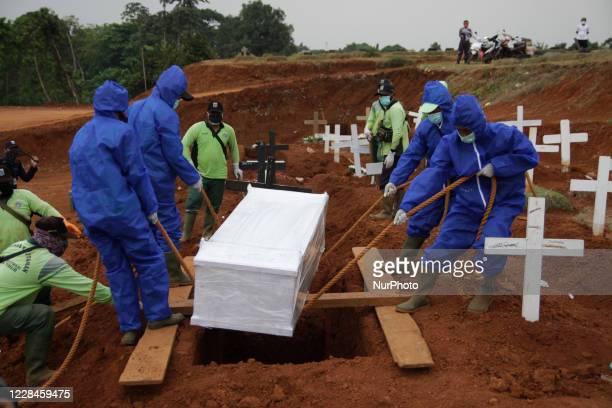 Gravediggers burying the body of Covid-19 coronavirus victim at Pondok Ranggon cemetery complex, Jakarta, on September 11, 2020. Pondok Ranggon...