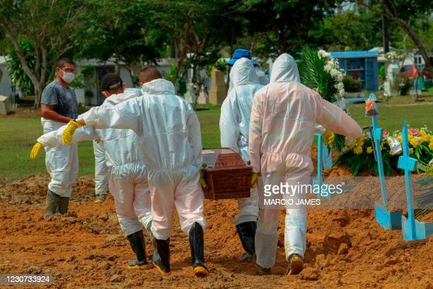 Gravediggers carry the coffin of a COVID-19 victim at the Nossa Senhora Aparecida cemetery in Manaus, Amazonas state, Brazil, on January 22 amid the...