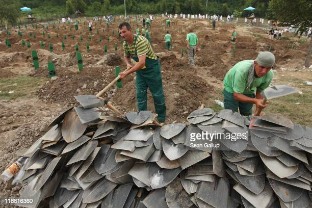 Gravediggers collect shovels following a mass funeral attended by tens of thousands of mourners for 613 newly-identified victims of the 1995...