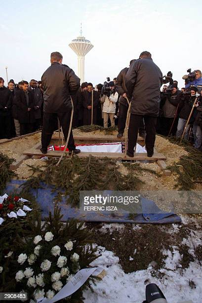 Gravediggers lower the coffin of Hungarian soccer player Miklos Feher into a grave 28 January 2004 during his funeral in Gyor 120 km east from...