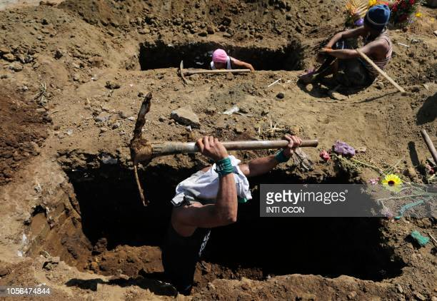 Gravediggers make new graves at the Milagro de Dios cemetery in Managua during the Day of the Dead on November 2 2018