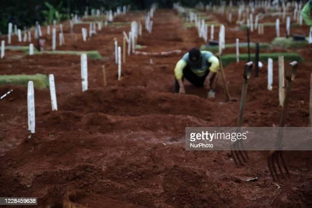Gravediggers take a rest at burial site for Covid-19 coronavirus victims at Pondok Ranggon cemetery complex, Jakarta, on September 11, 2020. Pondok...