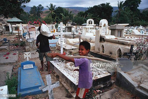 Gravediggers walk past the grave of Sebastiao Gomes in the Santa Cruz cemetery This was the site of a massacre by the Indonesian Army in 1991 when...