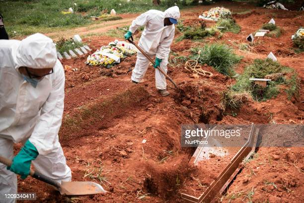 Gravediggers wearing protection against contamination bury the body of a dead man on suspicion of Covid19 in the cemetery of Vila Alpina east side of...