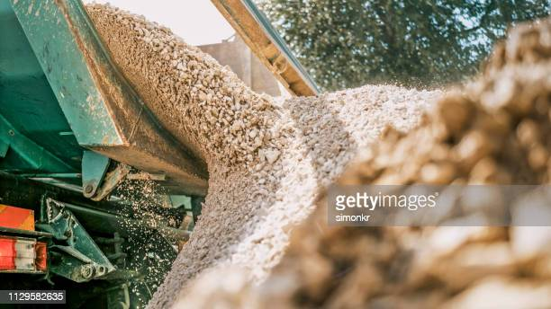 gravel falling of digger at construction site - gravel stock pictures, royalty-free photos & images