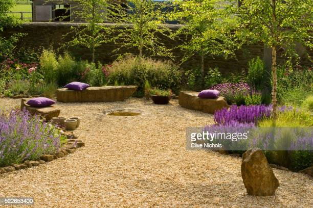 gravel garden with rock seats and wild flowers - seat stock pictures, royalty-free photos & images