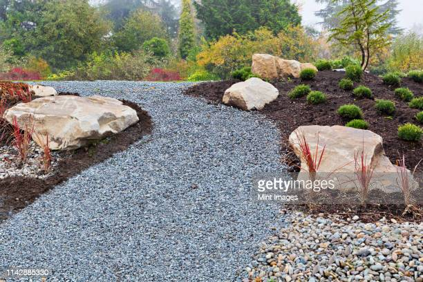 gravel path and rocks in landscaped garden - landscaped stock pictures, royalty-free photos & images
