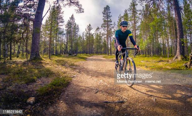 gravel road cyclist coming downhill on a narrow dirt road in the finnish lapland - gravel stock pictures, royalty-free photos & images