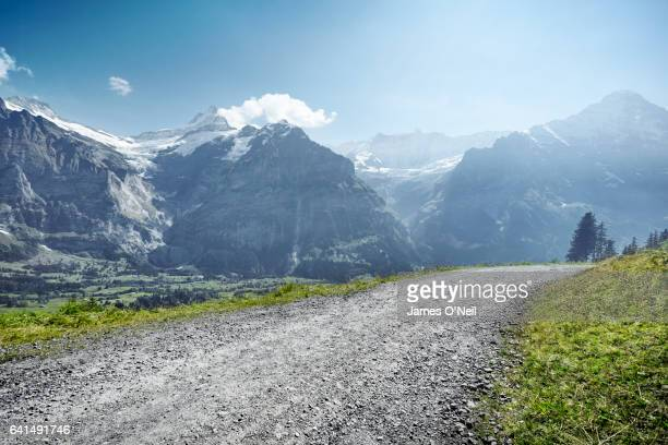 gravel road through mountain range - gravel stock pictures, royalty-free photos & images