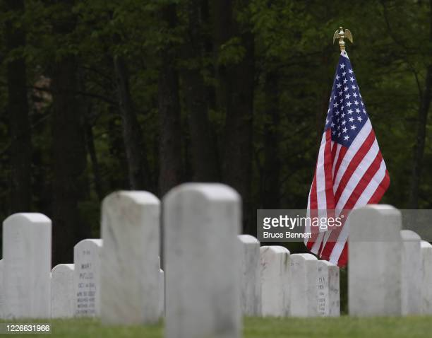 Gravesites are decorated with American flags at Calverton National Cemetery on May 23 2020 in Wading River New York Health guidelines due to the...