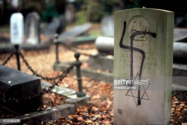 gravestone of jewish soldier painted with nazi swastika - anti semitism stock pictures, royalty-free photos & images