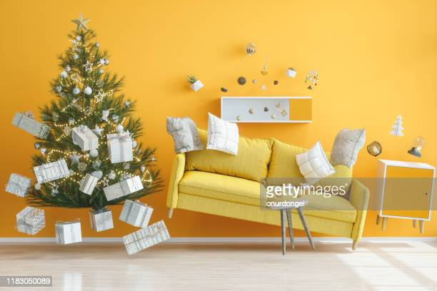 concepts de gravité. salle de séjour jaune avec l'arbre de noel - voler photos et images de collection