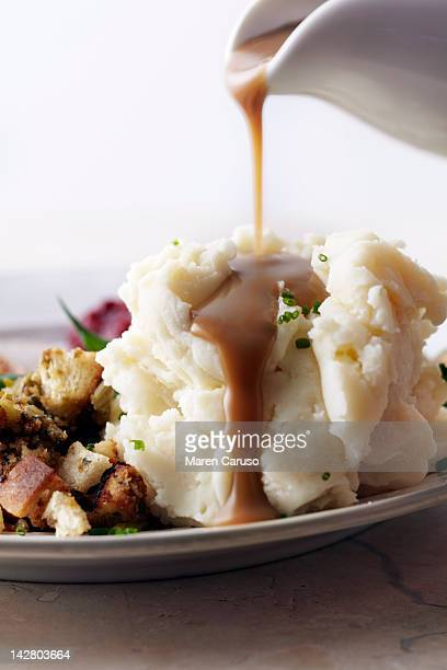 Gravy being poured onto mashed potatoes